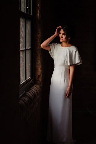 model in a white dress standing facing a window with a hand held up to her hair