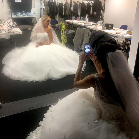 two models in wedding dresses. One is taking a photo of the other