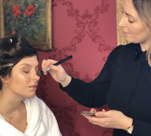 Kelly Daun applying makeup to a client