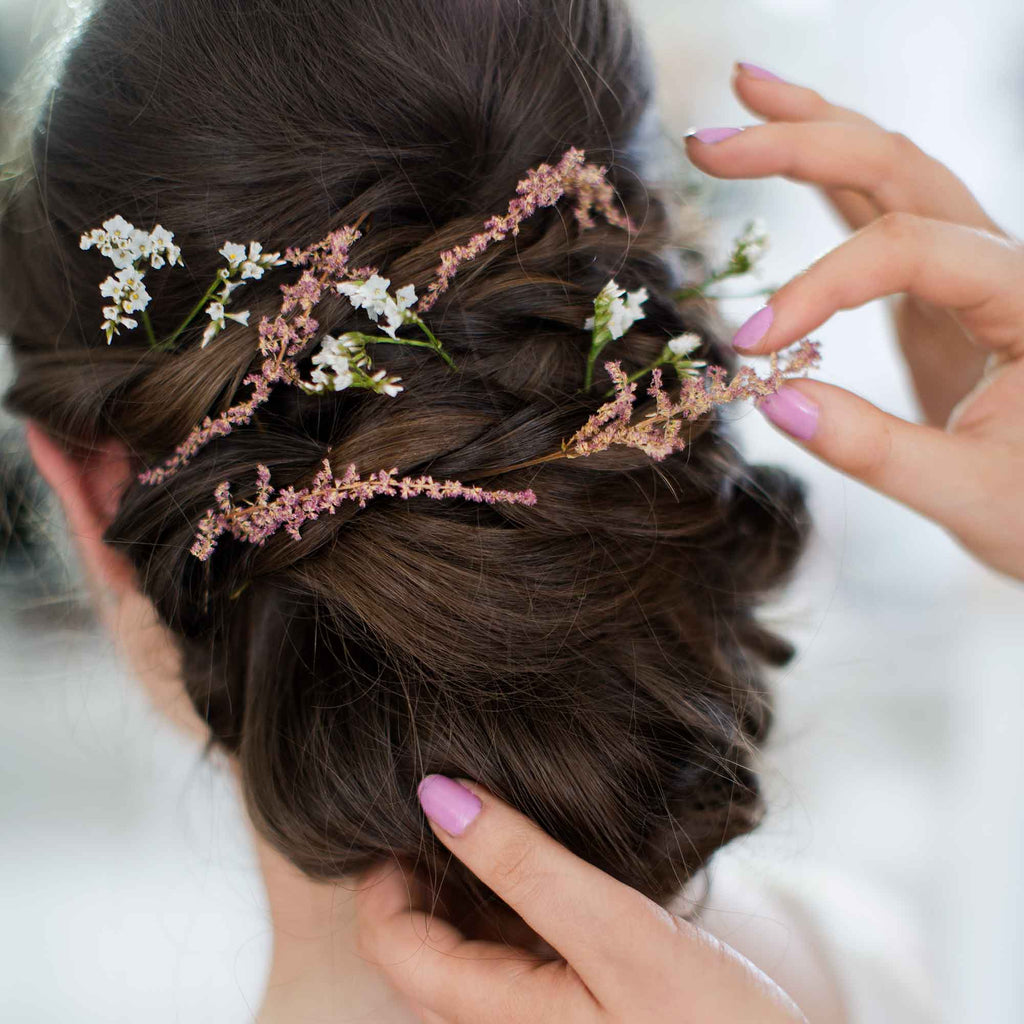 A hair tutor places a flower in a beautiful hair-do