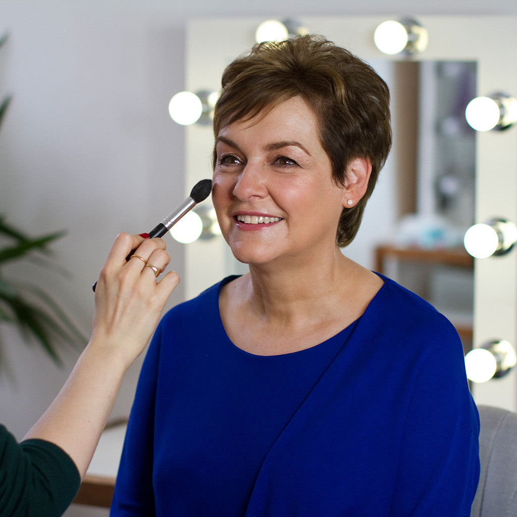 Applying makeup to a mother of the bride