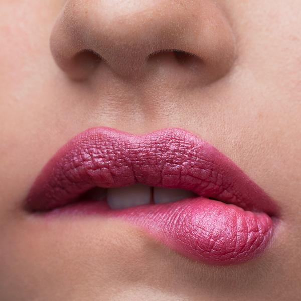 Close up of model biting her lip while wearing Grace Lipstick
