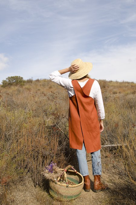 person modeling a clay colored pinafore apron made of linen fabric. They are wearing jeans and a white long sleeved shirt.