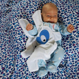 Smiling baby lying on blue leopard muslin with white & blue heart style comforter by The Dou-Doods