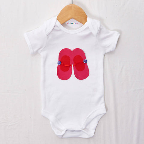 Pink and red ballet shoes on a White baby grow, size 0-3 months