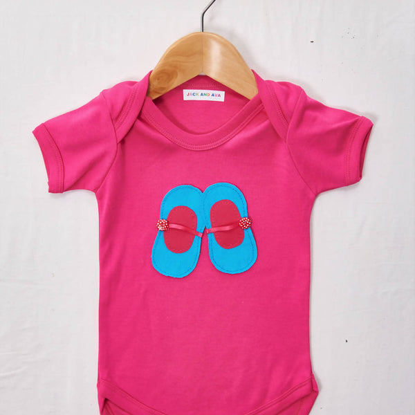Blue and pink ballet shoes on a Pink baby grow, size 0-3 months