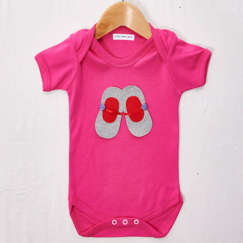 Grey and red ballet shoes on a Pink baby grow, size 0-3 months