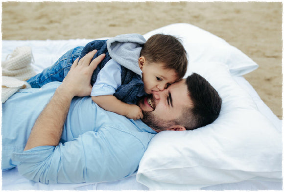 Young father and his son on an Organic Adjustable Loft Pillow by A Little Pillow Company