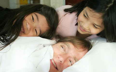A father and his two daughters on a bed with A Little Pillow Company pillows