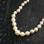 Vintage 1940's Cultured Pearl Necklace close up on a black leather background