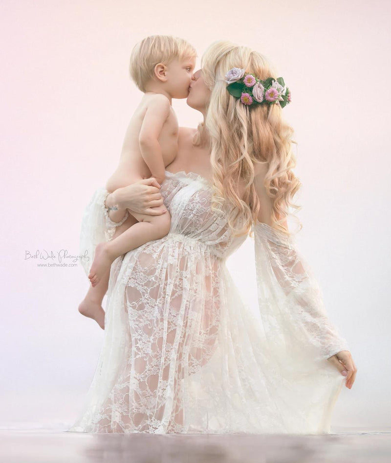 Pregnant mother wearing the Valerie in ivory by Sew Trendy standing in ocean holding son