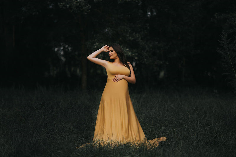 Pregnant Mother in the Macey Gown by Sew Trendy Accessories in Gold standing in a green field.
