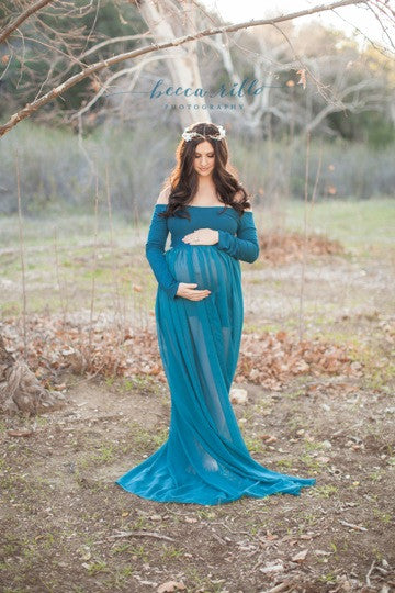 Pregnant woman in the Roxy Gown in Jade by Sew Trendy Accessories standing in a golden field with trees.