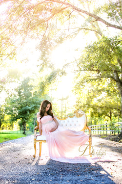 Pregnant mother in the Lexcie Gown in Blush by Sew Trendy Accessories sitting in a chair with trees in the background.