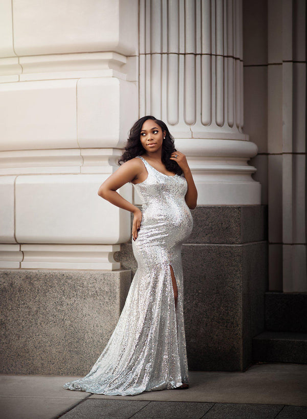 Pregnant mother in the Marcie Gown by Sew Trendy Accessories in Silver Sequin standing in front of a building.