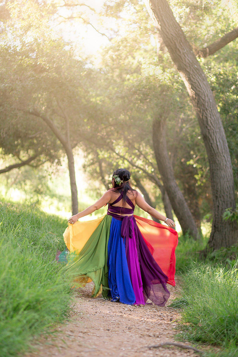 Pregnant woman in the Miracle Gown in Jewel Tones by Sew Trendy Accessories walking in the woods.