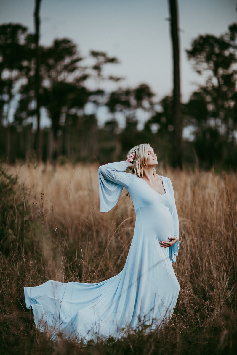 Pregnant mother in the Lennon Gown by Sew Trendy Accessories in Blue Rain in a golden field.