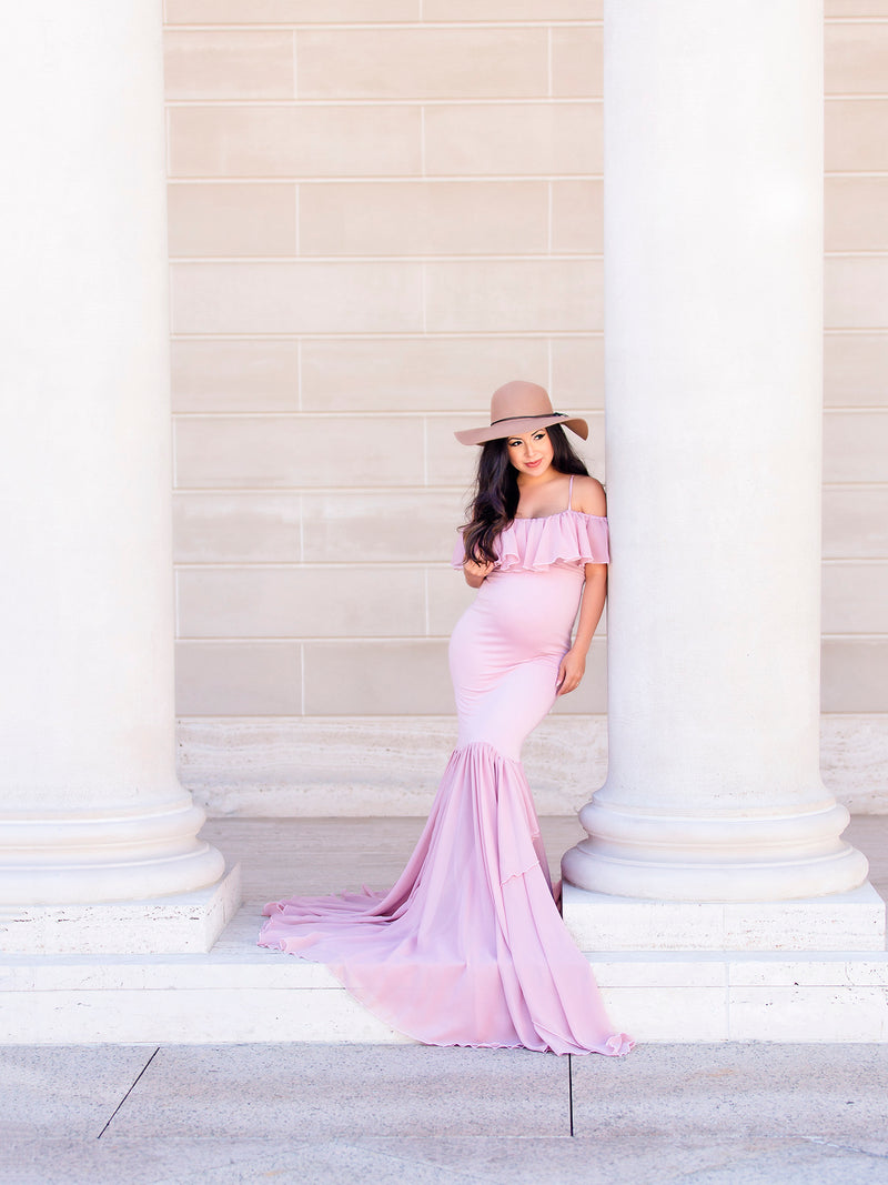Beautiful expecting mother wearing the Camilla gown in mauve by Sew Trendy standing next to large white columns