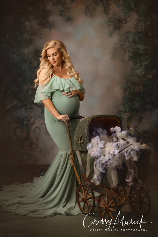 Beautiful blonde expecting mother wearing the Camilla gown in Sage by Sew Trendy standing in studio with baby carriage and florals.