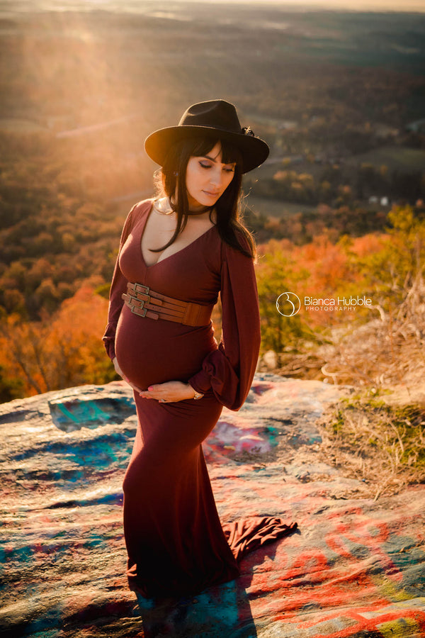 Pregnant woman wearing the Florence gown in redwood by Sew Trendy standing on grafitti rock at sunset