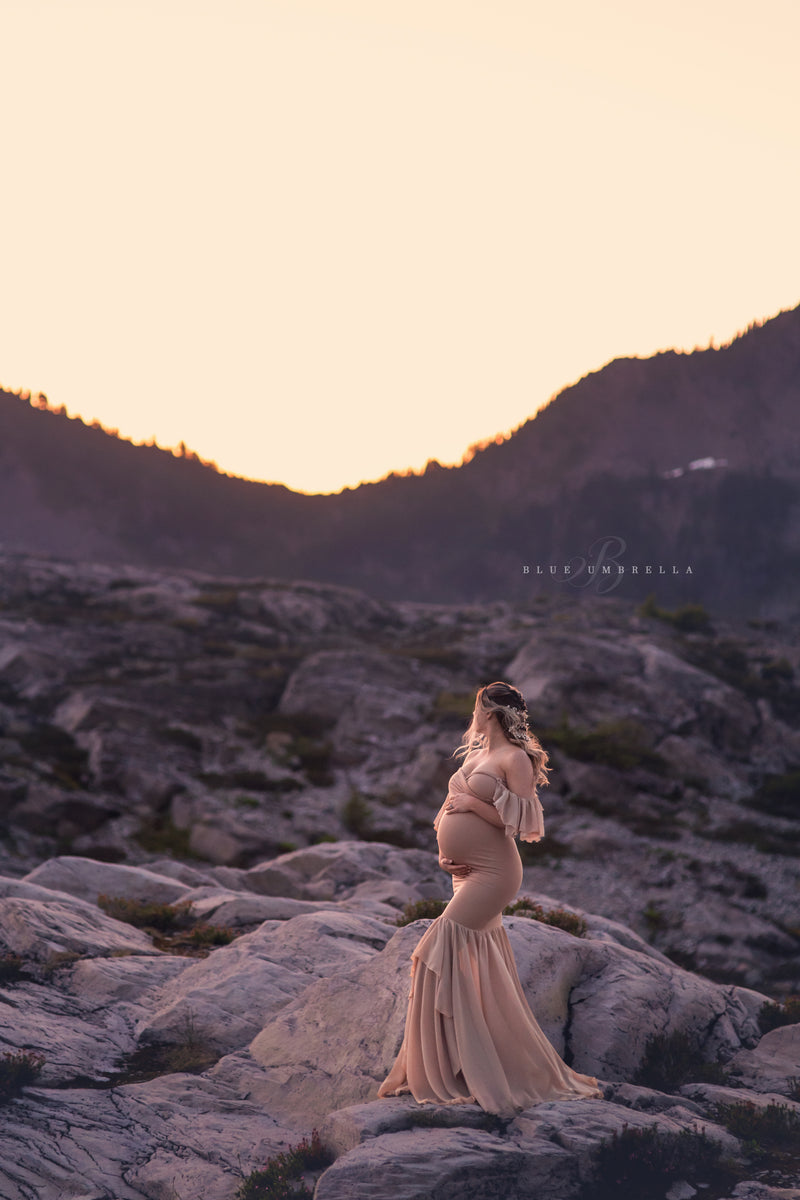 Pregnant woman in the Sable Gown in Camel by Sew Trendy Accessories standing with mountains in the background.