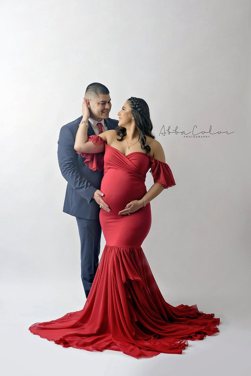 Expecting mother wearing the Sable gown in red by Sew Trendy standing with her husband iin studio