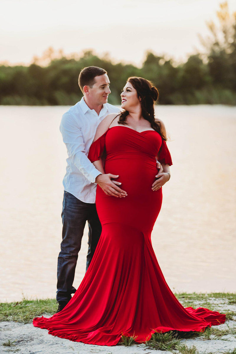 Expecting mother wearing the Serenity in red by Sew Trendy standing with husband near lake