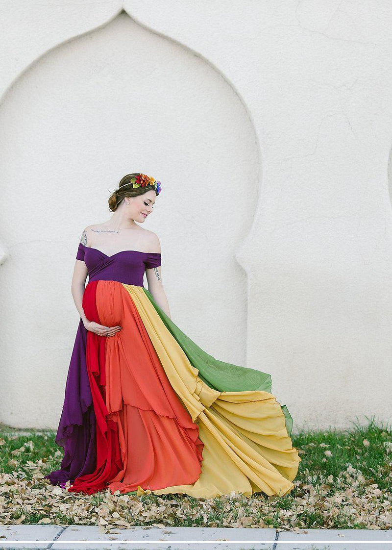 Pregnant mother wearing the Hope Gown in Jewel Tones by Sew Trendy Accessories in front of a stone building.