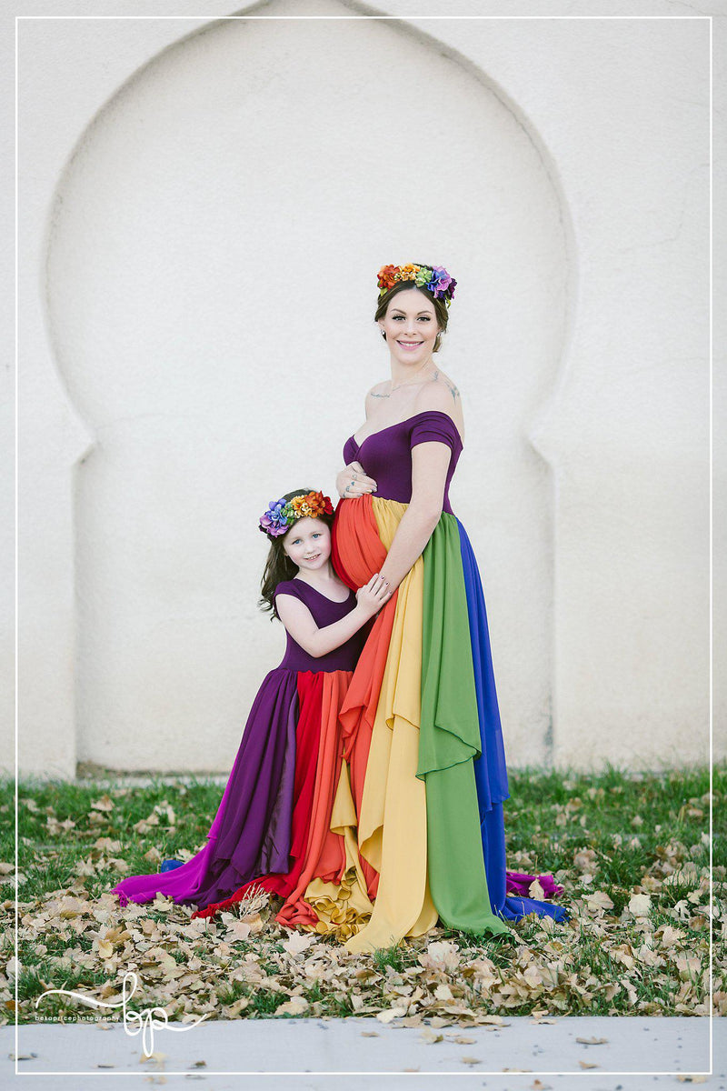 Pregnant mother wearing the Hope Gown in Jewel Tones by Sew Trendy Accessories in front of a stone building with a littler girl.