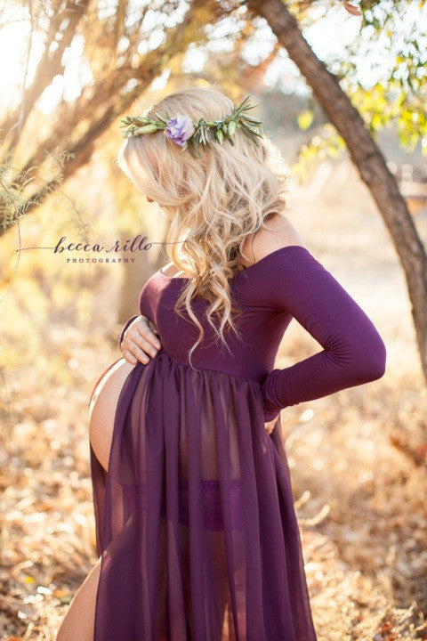 Pregnant woman in the Roxy Gown in Plum by Sew Trendy Accessories standing in a golden field with trees.