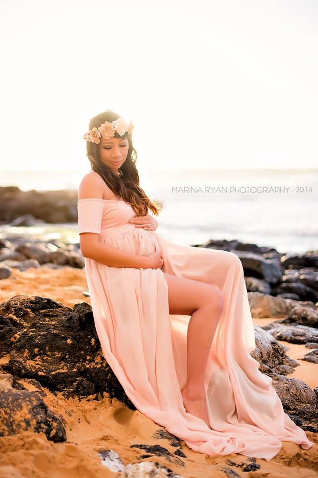 Expecting mother wearing the Cameron gown in blush by Sew Trendy sitting on beach
