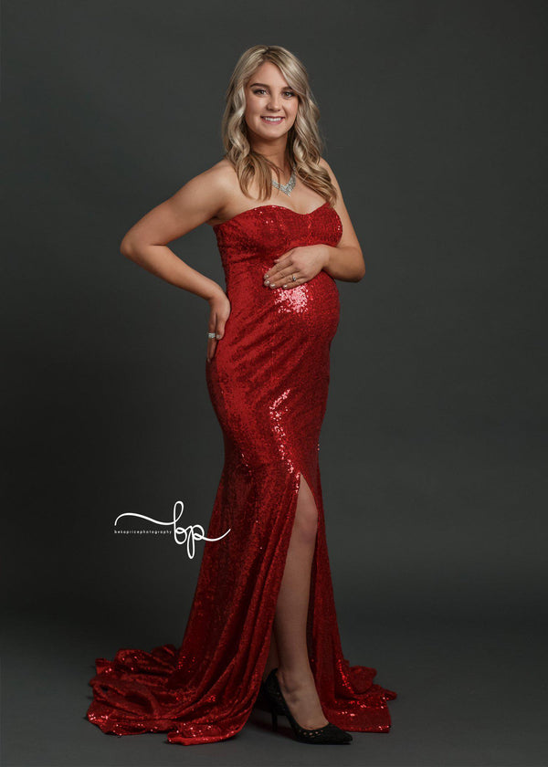 Pregnant mother in the Jessica Gown in Red Sequin by Sew Trendy Accessories in the studio with a grey backdrop.