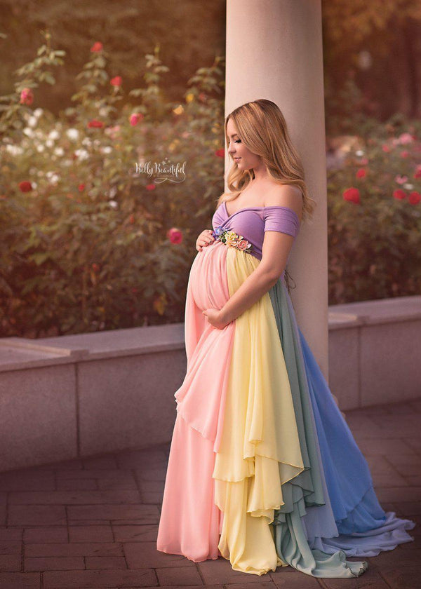 Pregnant mother wearing the Hope Gown in Pastel Tones by Sew Trendy Accessories with flowers in the background.