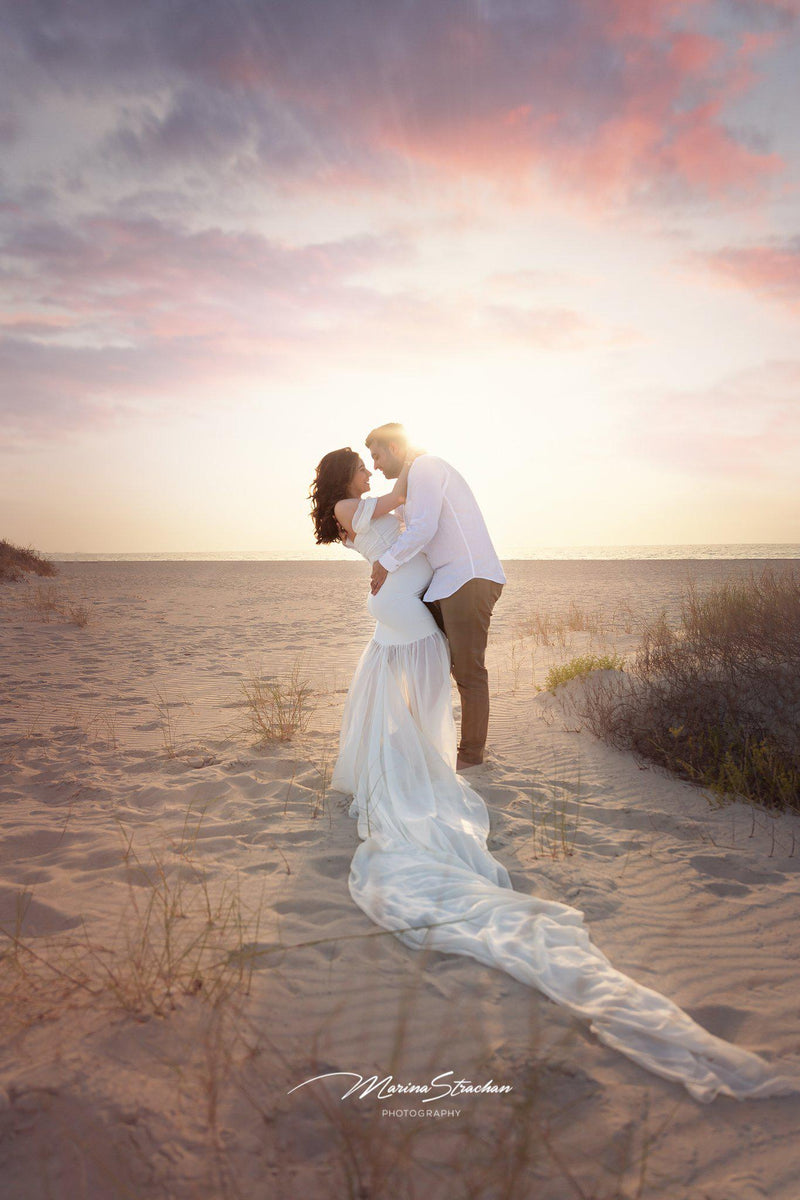 Expecting mother wearing the Angela gown in ivory by Sew Trendy, standing on beach embraced by husband.