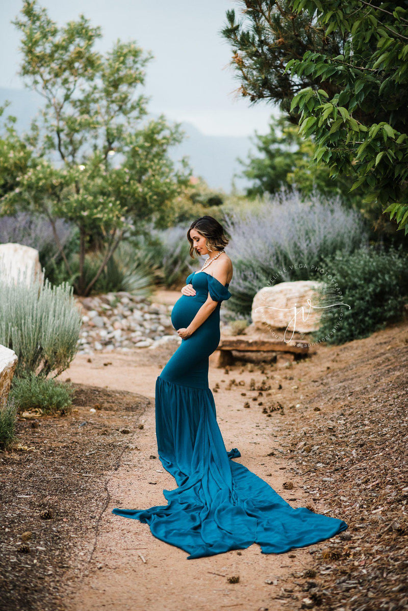 Expecting mother wearing the Angela gown in teal by Sew Trendy, standing on garden path.