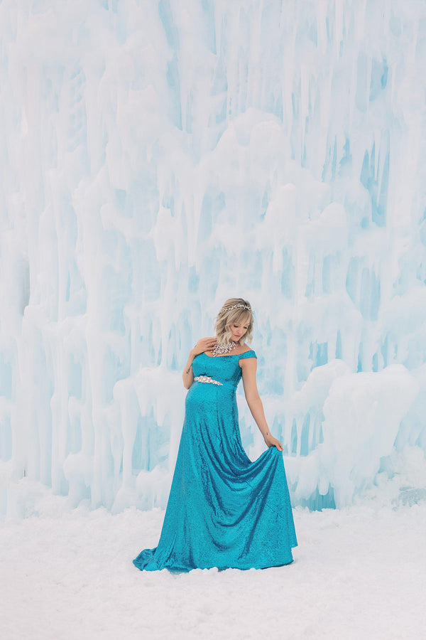 Pregnant woman wearing the Breah gown in sequin by Sew Trendy standing in front of ice castles