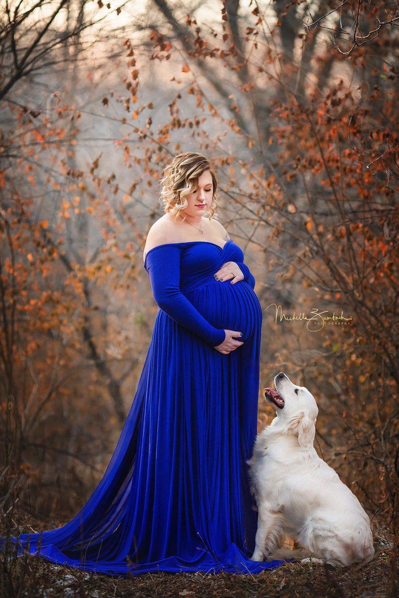Pregnant woman standing in autumn forest wearing the Breanna gown in royal blue by Sew Trendy.