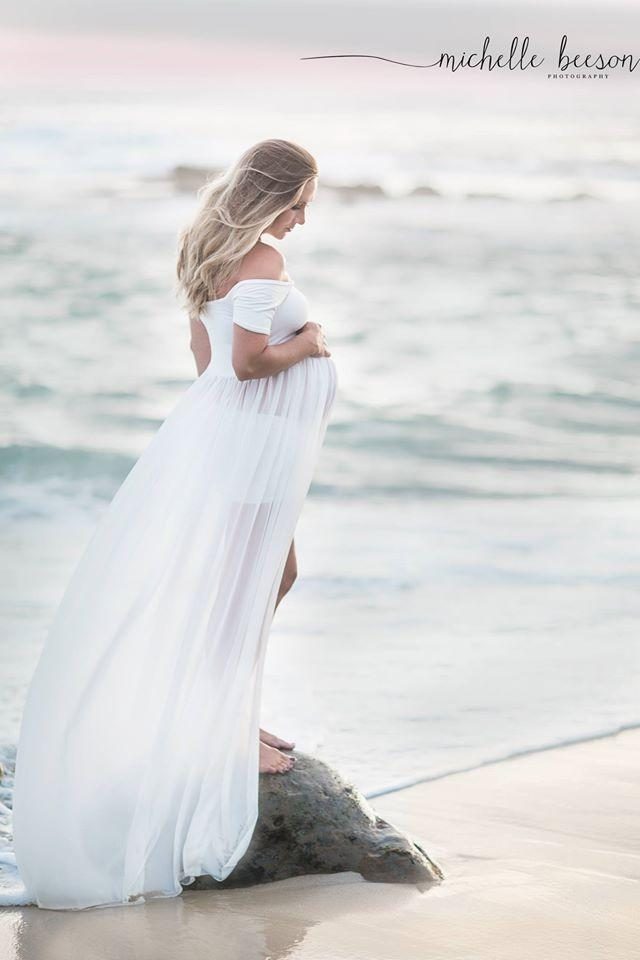 Expecting mother wearing the Cameron gown in white by Sew Trendy standing on pastel beach