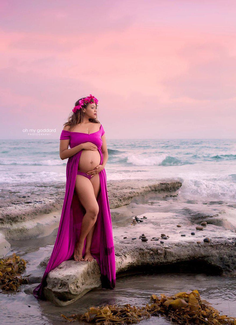 Pregnant Mother in the Kiara gown by Sew Trendy Accessories in Magenta standing on the beach.