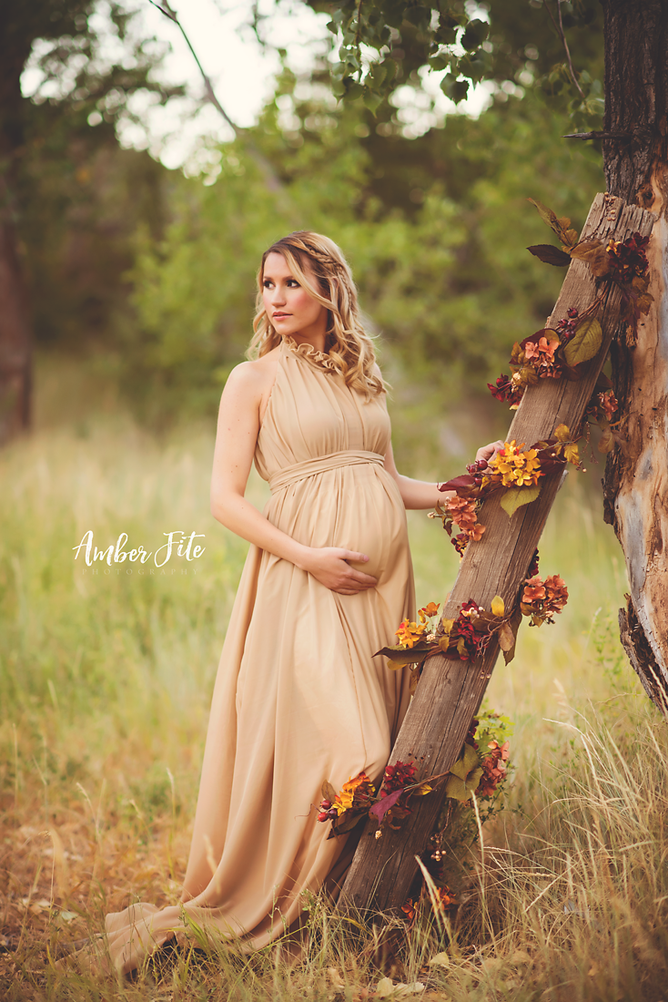 Pregnant woman wearing the Carolynne gown in Camel by Sew Trendy standing on forest path