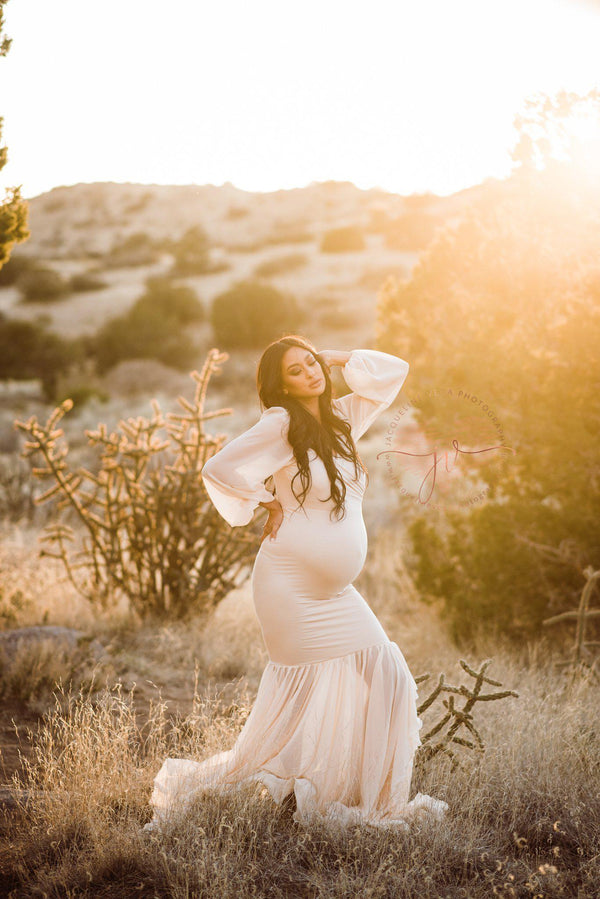 Pregnant mother wearing the Francis gown in champagne by Sew Trendy standing in a desert field at sunset