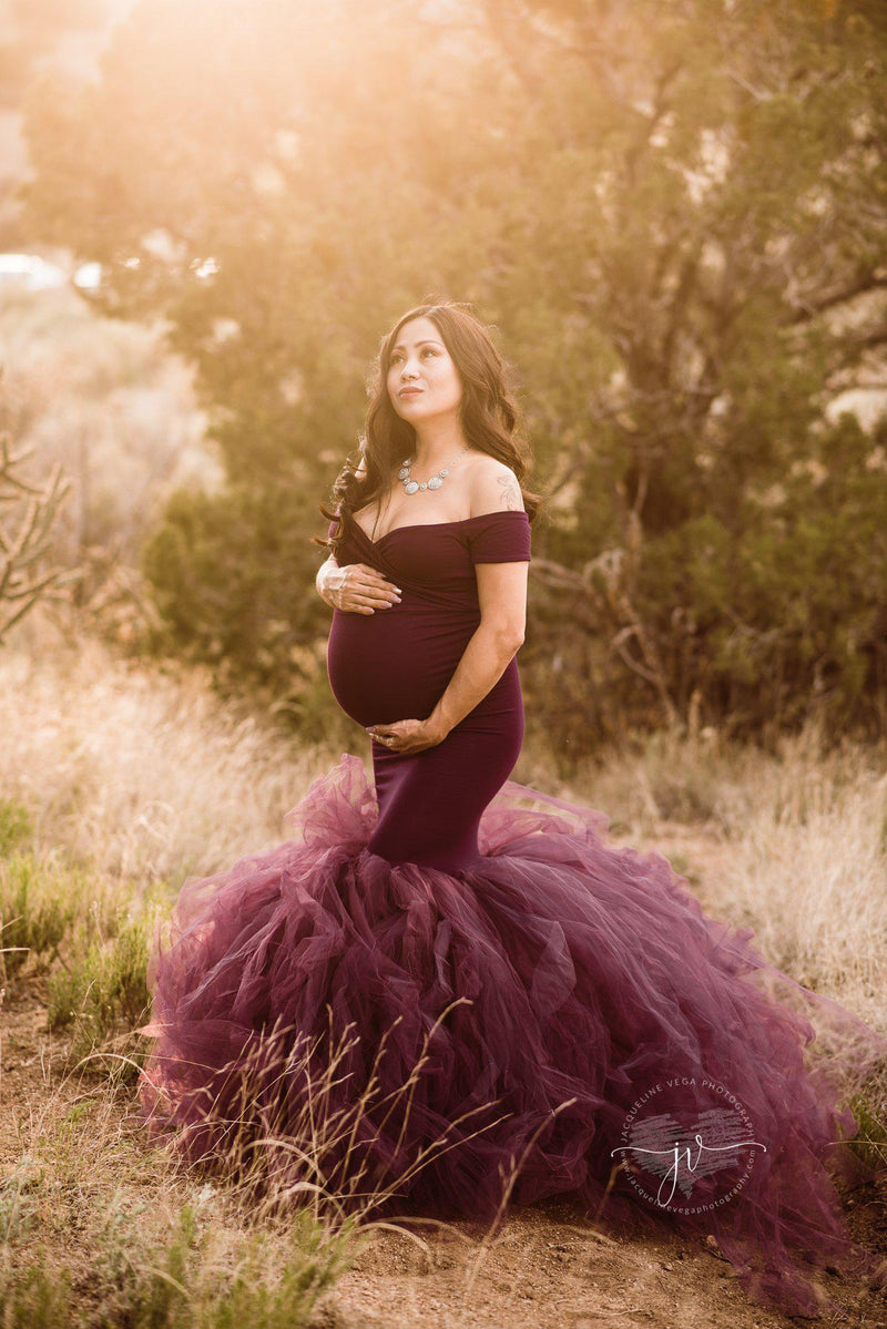 Pregnant mother in the Jacqueline Gown in Plum by Sew Trendy Accessories in a field with trees.