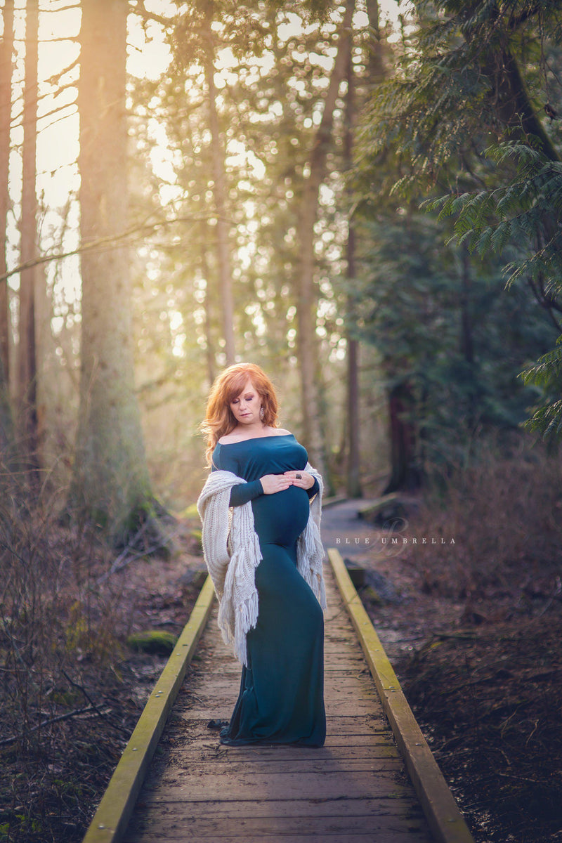 Pregnant mother in the Jaden Gown in Teal by Sew Trendy Accessories on a bridge in the forest.
