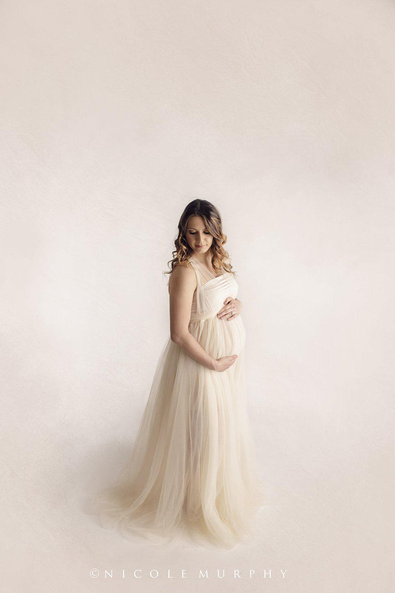 Pregnant mother in the Kaitlyn Gown by Sew Trendy Accessories in Ivory in the studio.