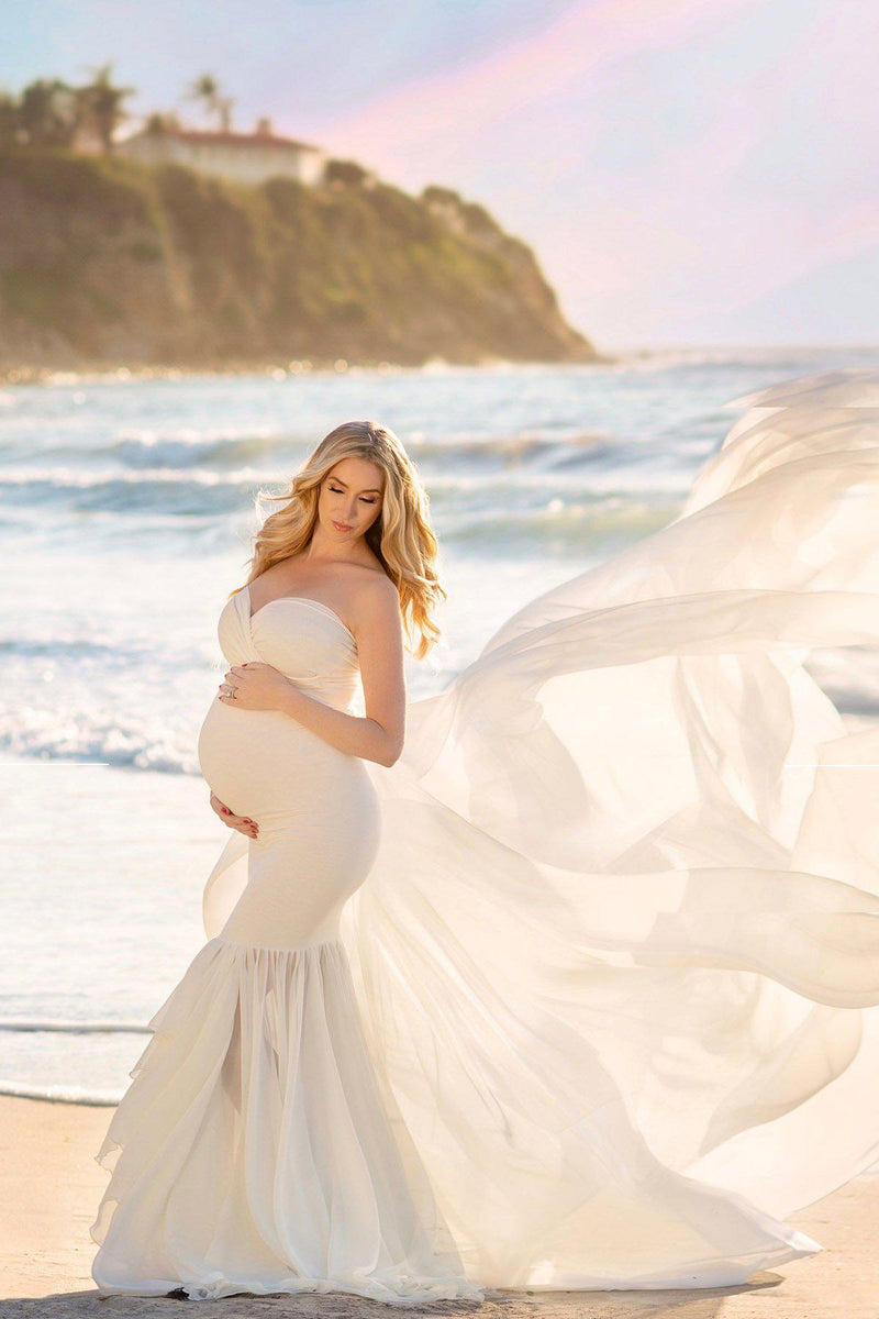 Pregnant mother in the Liv Gown by Sew Trendy Accessories in Ivory standing on the beach.