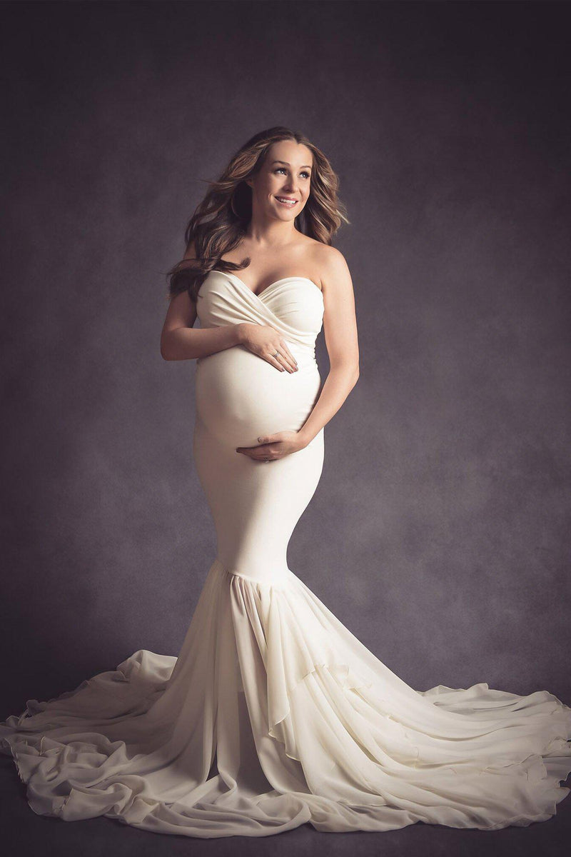 Pregnant mother in the Liv Gown by Sew Trendy Accessories in Ivory in a studio with a dark background.