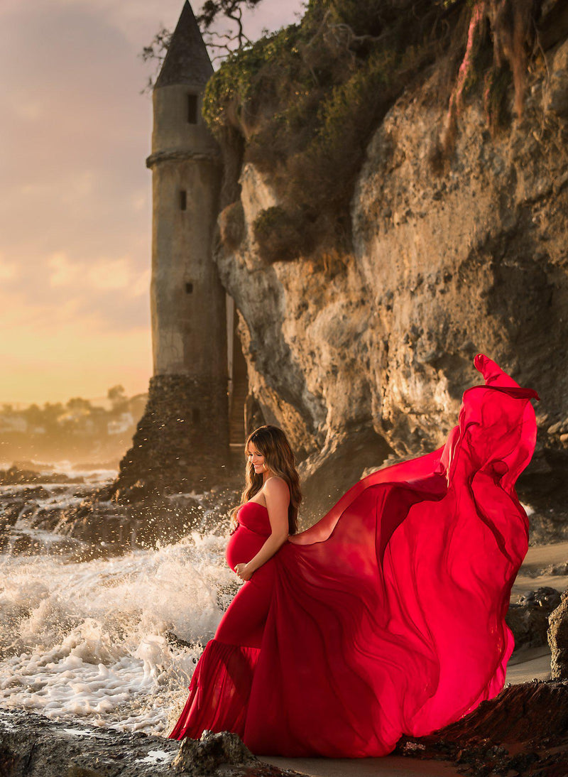 Pregnant mother in the Liv Gown by Sew Trendy Accessories in red standing on the beach with a castle in the background.