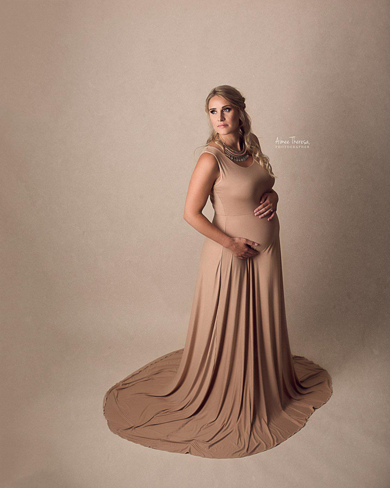 Pregnant Mother in the Macey Gown by Sew Trendy Accessories in Camel in the studio with a tan background.