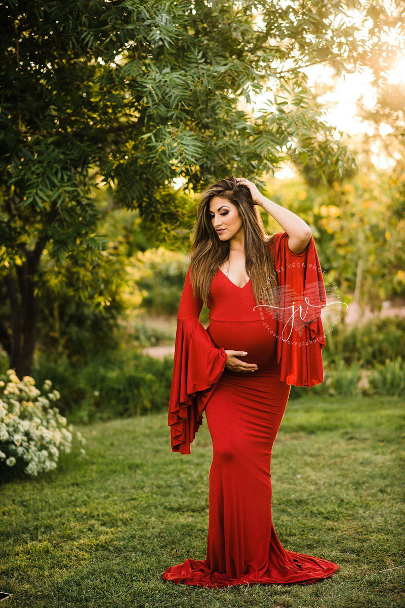 Pregnant mother wearing Veda gown in red by Sew Trendy standing in sunkissed tree grove