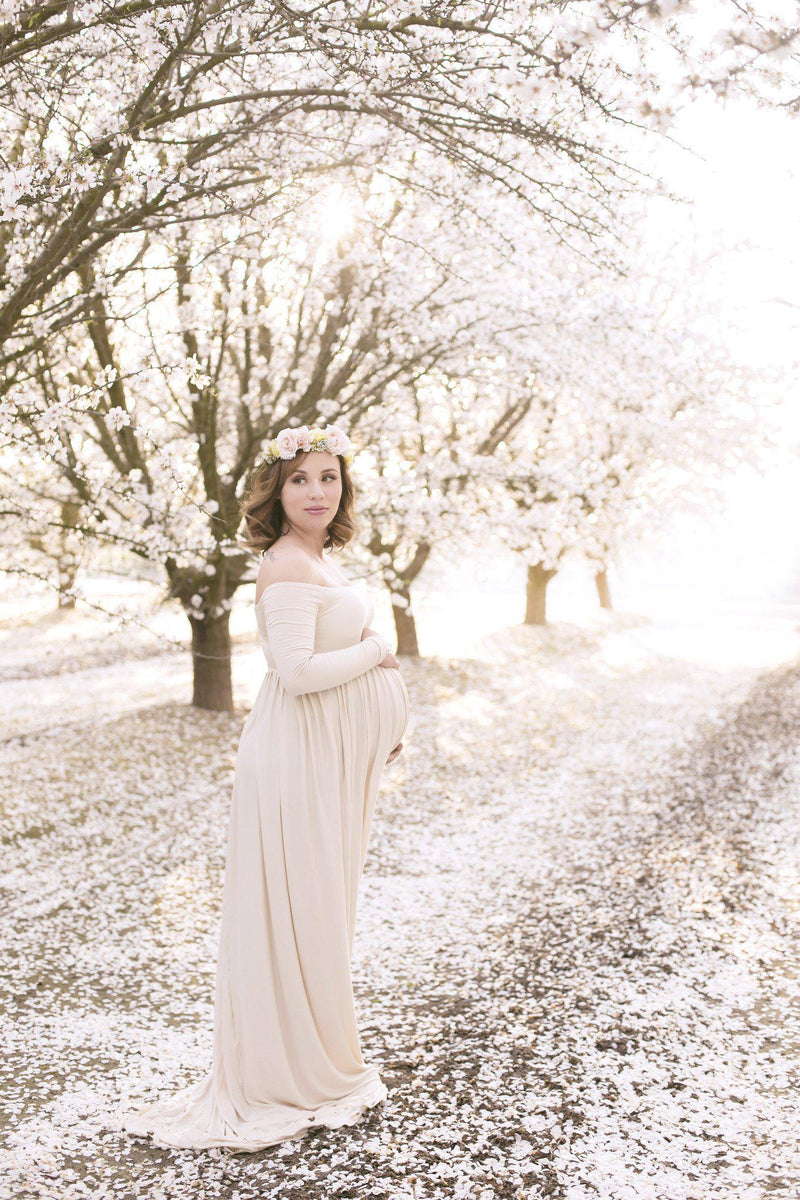 Pregnant woman in the Miriam Gown in Blush by Sew Trendy Accessories standing on a path with tree blossoms.